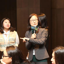 Hae-Jeong Lee speaks into a microphone as a student stands beside her