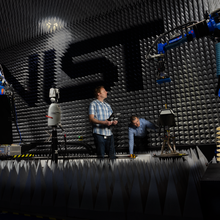 Researchers in large anechoic chamber with NIST logo on wall looking at robotic arms and equipment.