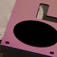 A flat pink device with a round black patch lies over a quarter.