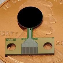 A small flat device with a round black part and a copper-colored rectangular part lies on top of a penny.