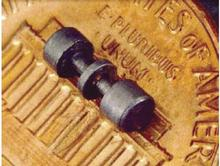 "This image shows the electrodes of an ion trap used to trap mercury ions.  The electrodes are placed on a US penny to show scale, and are about the size of the text ""E Pluribus Unum\""."