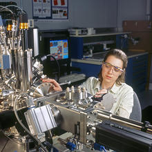 postdoctoral researcher Lucile Teague inserts a sample into a scanning tunneling microscope to study the electrical behavior of organic molecules on a gold surface.