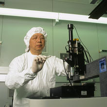"Researcher Stephen Hsu prepares to measure nanoscale friction between a diamond tip and a silicon surface in a NIST Advanced Measurement Laboratory sophisticated low-vibration ""clean rooms."""