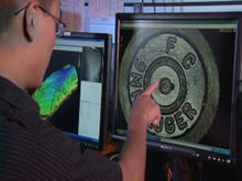 NIST engineer pointing at a firing pin impression.