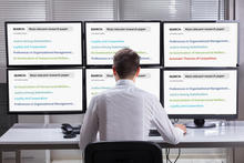 A man facing six computer screens sees six different sets of search results, with each listed item color-coded.