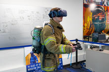 This image shows a man in firefighter uniform wearing a VR headset