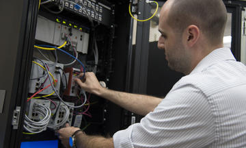 Timothy Zimmerman checking connections in the Cybersecurity for Smart Manufacturing Systems testbed