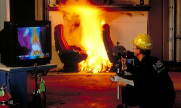 A fire engineer wearing black NIST jumpsuit and yellow hard hat is kneeling next to a tv screen displaying multiple colors of the yellow and orange fire burning on a chair in the background.