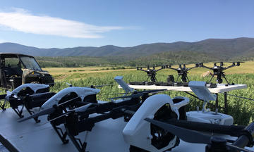Seven drones lined up on the ground before takeoff.