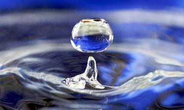 a drop of water springing up from a pool