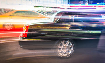 A streaked image of a taxi and a dark car driving in Times Square, New York City street at night.