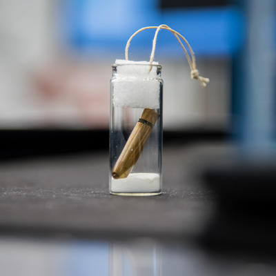 A copper bullet in a glass jar, sealed at the top.