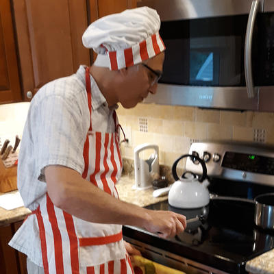 Zach Levine in his kitchen wearing an orange and white striped apron and chef's hat