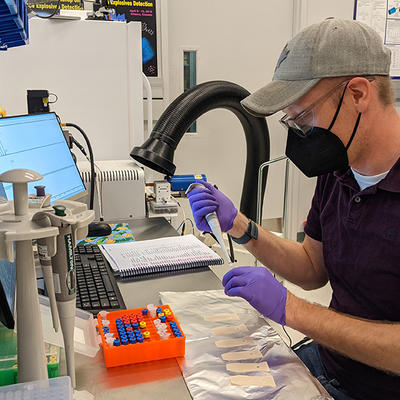 masked man with baseball cap seated at a lab bench pipetting samples