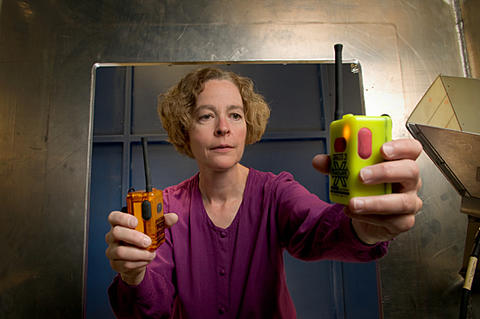 NIST engineer Kate Remley holds two Personal Alert Safety System (PASS) devices with wireless alarm capability.