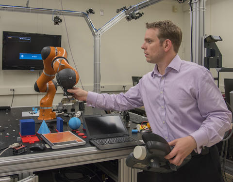 Jeremy Marvel adjusts robotic arm