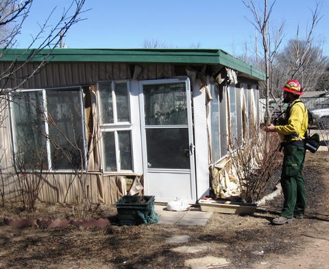 A member of a joint NIST-Texas Forest Service study team collects data on a Amarillo, Texas, building damaged by wildfires in February 2011.