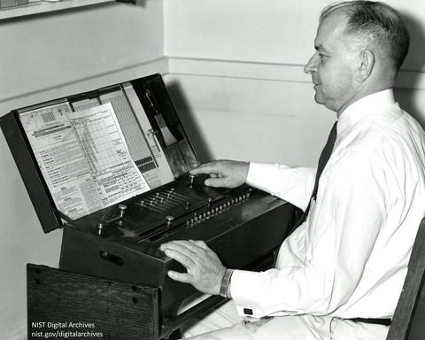 Harry Keegan seated at mechanical calculator CIE color coordinates of standard sources, 1958