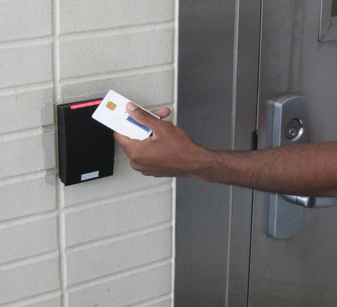 Photo of a person holding a PIV card up to a reader