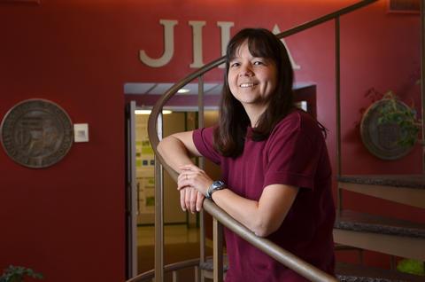 Deborah Jin standing on the staircase at JILA