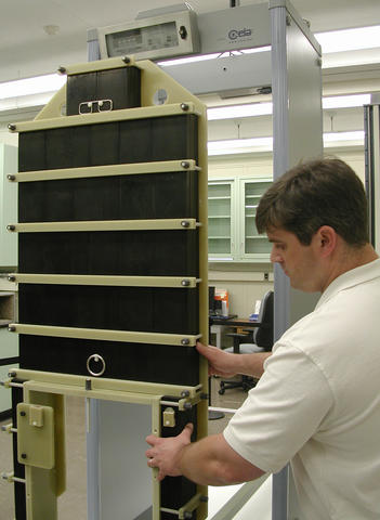 Guest researcher John Jendzurski prepares the NIST electromagnetic phantom for passage through the walk-through metal detector behind it.