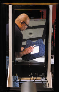 NIST engineering technician Nathaniel Waters examines a bullet-resistant vest being tested