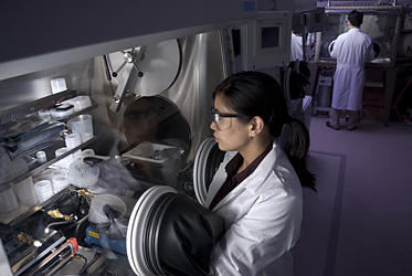 NIST researcher Leah Lucas examines thin film transistors made on plastic rather than silicon using a protective glove box.