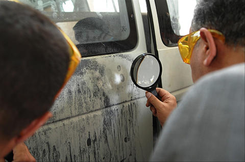 Law enforcement officers locating latent fingerprints on the side of a van.