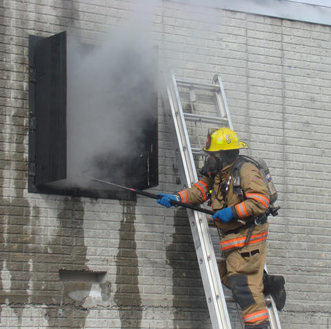 During a fire safety experiment, a firefighter ventilates the building to let smoke and heat out to improve conditions inside.