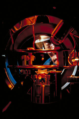 Researcher Kris Helmerson observes a tiny glowing cloud of sodium atoms caught by six intersecting laser beams in a vacuum chamber.