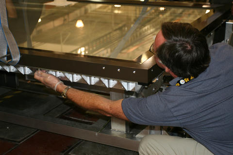 NIST technician putting bolts into the map encasement