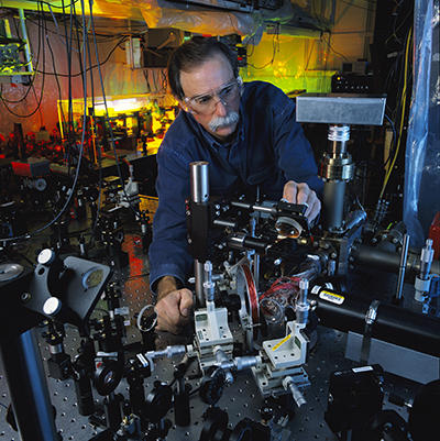 David Wineland leans over a table of lasers to adjust a laser beam