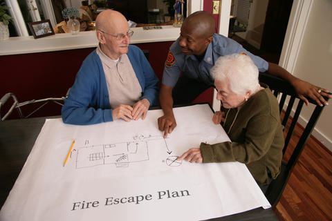 Three people looking at drawing of Fire Escape Plan