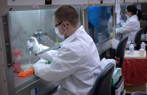 Man in white lab coat using a pipette under a hood