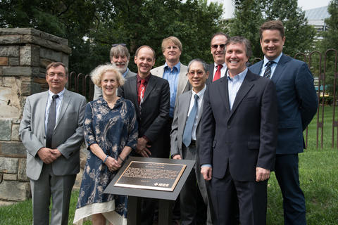 Various NIST employees with the posing with plaque commemorating the invention of the atomic clock on the campus of what is now the University of the District of Columbia