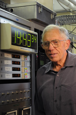 Man with gray hair standing beside computer with digital clock display