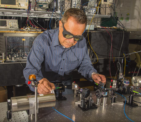 Man in striped shirt wearing laser safety glasses working with laser table in laboratory.