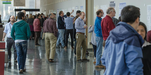 Scientific posters line a hallway. NIST postdocs and researchers stand in front of the posters discussing them.