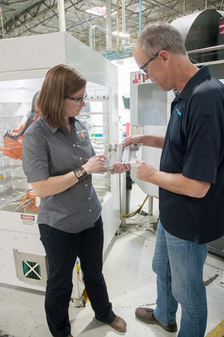 A man and a woman examine a part on a manufacturing floor
