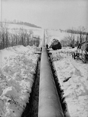 The Big Inch pipeline laid in its trench extending through a field of snow