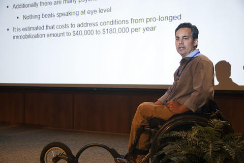 Man in a wheelchair presenting at a conference