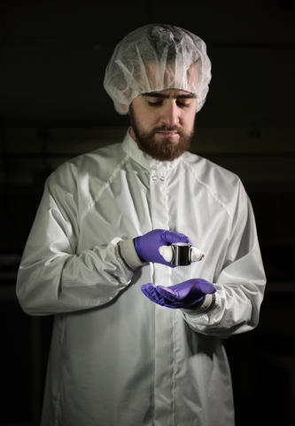 Man in clean suit and purple gloves holding a kilogram sample with tongs