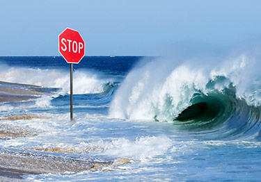 wave crashing over stop sign
