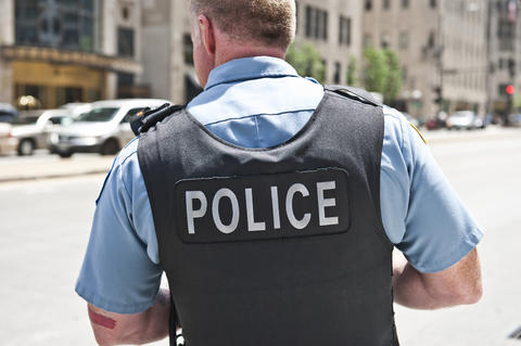 Photo of police officer from behind wearing body armor labeled Police