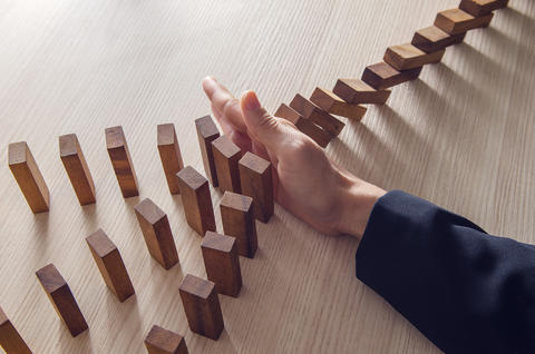 hand knocking over a line of blocks