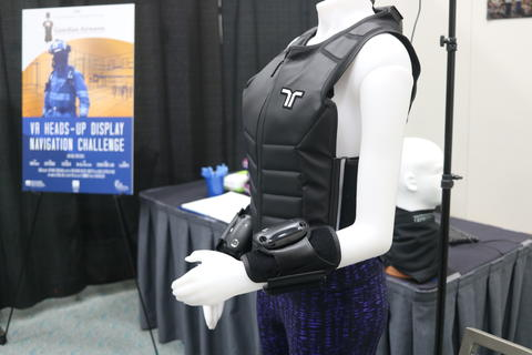 A vest lies on a mannequin next to a prize competitor's demonstration for their Virtual Reality prototype for the Virtual Reality Heads up Display Prize Challenge.