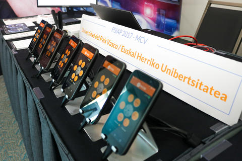 Several cellphones lined up at an award recipient's demonstration table at the 2018 Stakeholder Meeting
