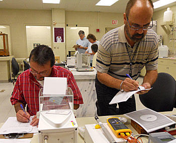Instructors perform measurements during dry run of Fundamentals of Metrology course