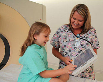 A nurse and young patient share a smile while preparing for a procedure at one of the units serving under the Charleston Area Medical Center Health System