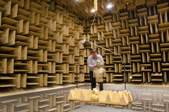 Randy Wagner prepares a standardized manikin for hearing aid testing in NIST's anechoic chamber.